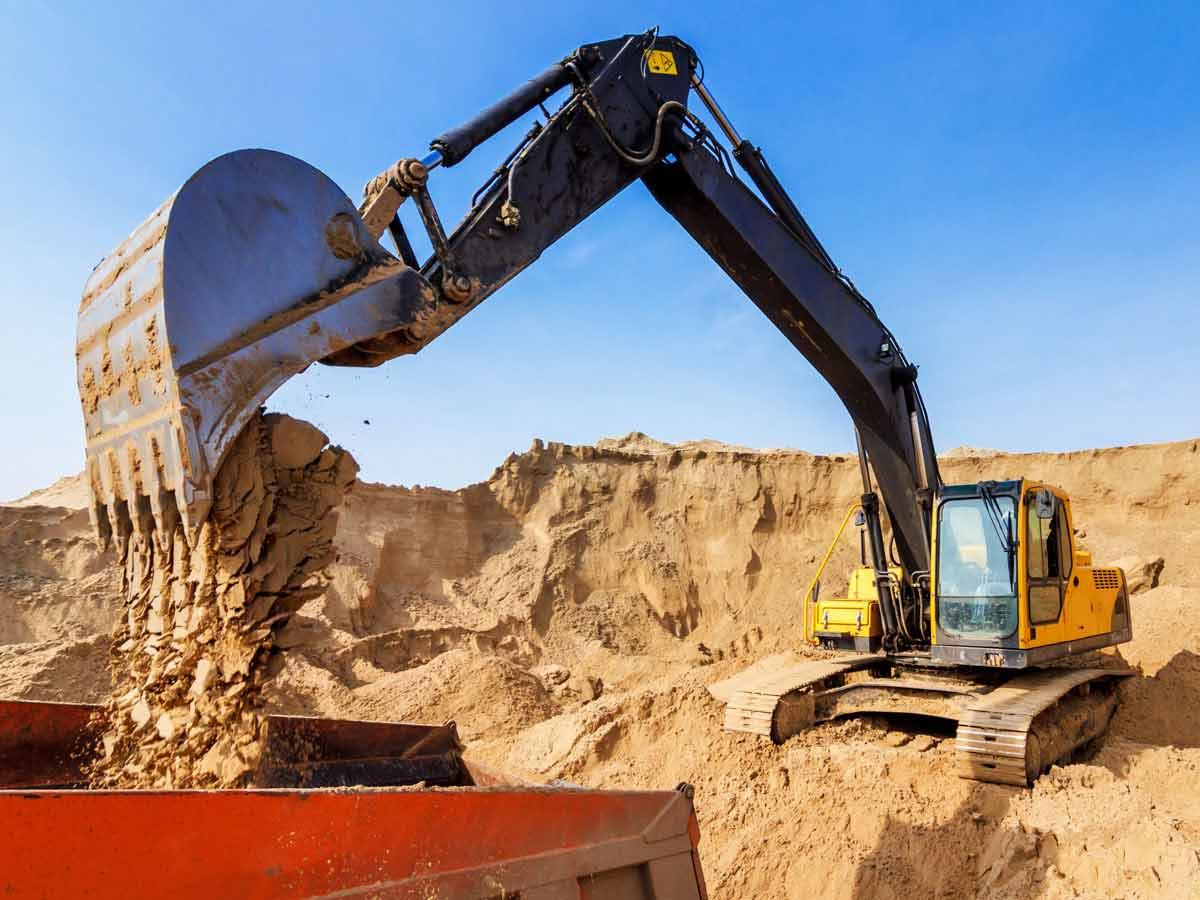 excavator loading truck at quarry
