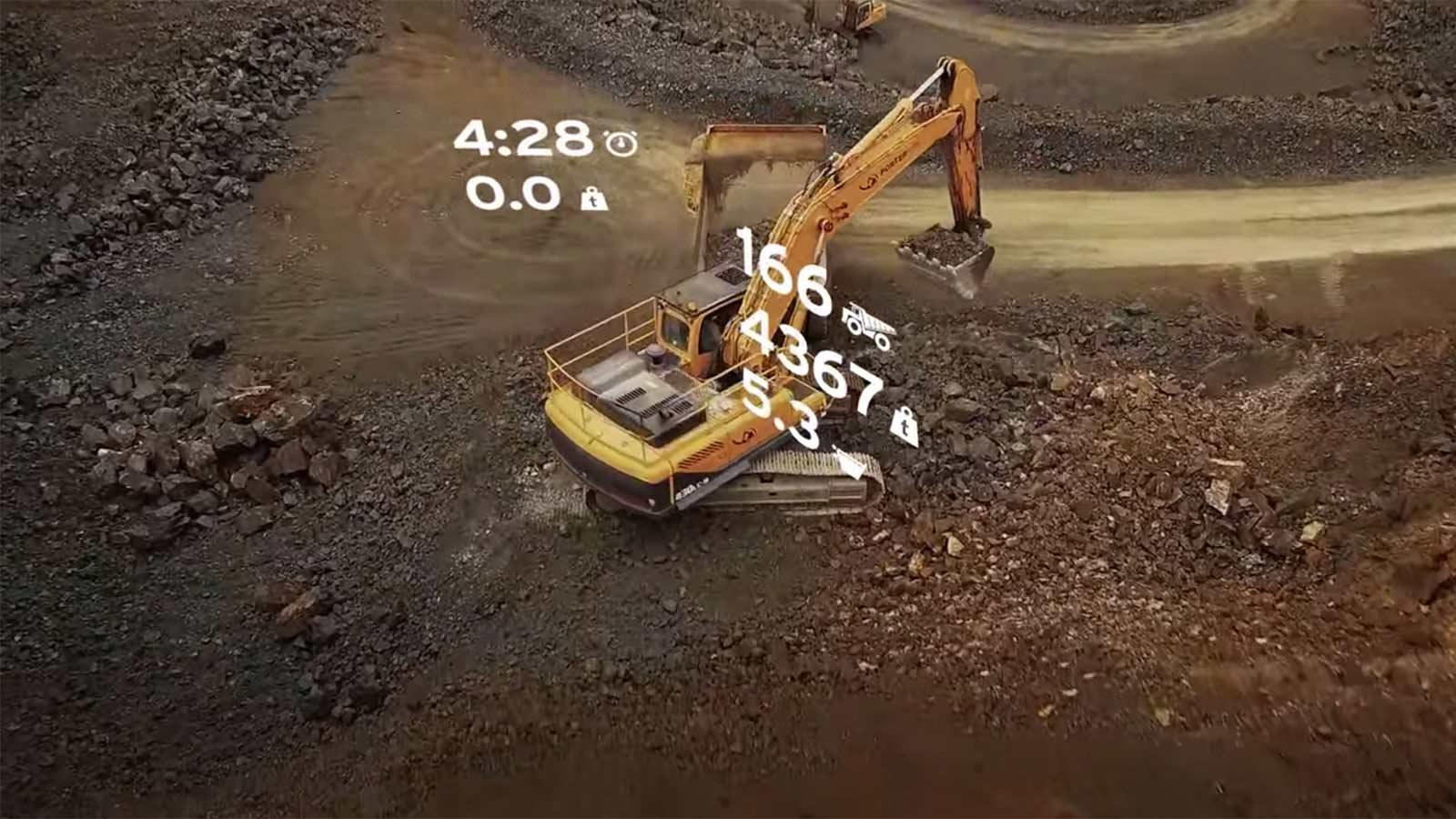 Aerial view of an excavator loading a truck with data overlay